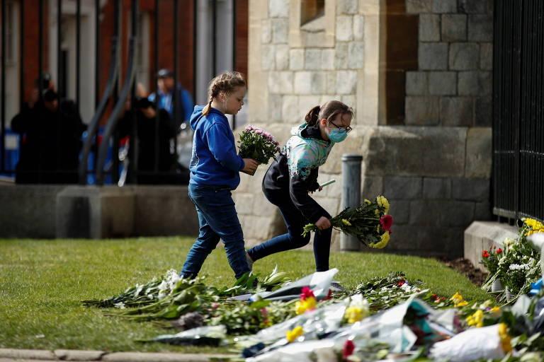 Crianças deixam flores do lado de fora do Castelo de Windsor após o anúncio da morte do príncipe Philip