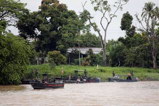 FILE PHOTO: Venezuelan soldiers patrol by boat on the Arauca River, the border between Colombia and Venezuela, as seen from Arauquita
