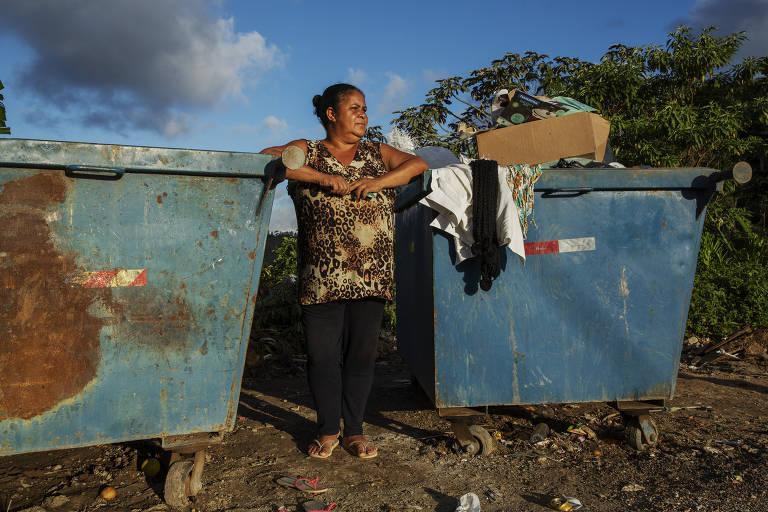 Marli Oliveira Gama, 54, conversa ao lado de caçambas onde costuma procurar por material reciclável para vender e até comida