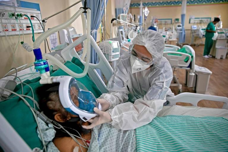agente de saúde com roupa de proteção atende paciente intubado no leito hospitalar