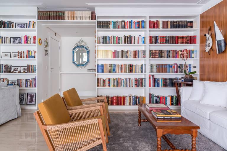 Sala com parede inteira de estantes, na cor branca