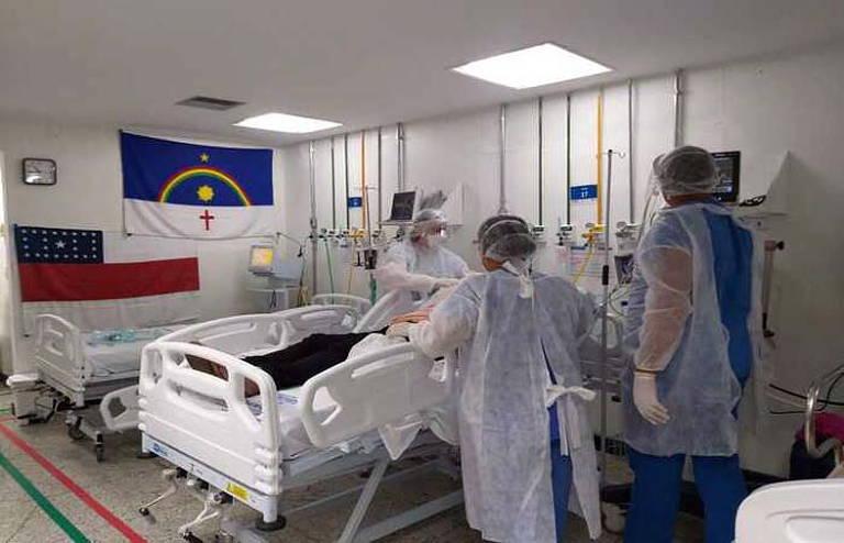 Três profissionais da saúde paramentadoscuidam de um paciente em um leito de UTI. Em uma parede, ha uma bandeira do Pernambuco.