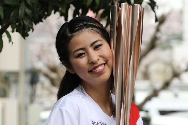 Mulher sorri abraçada à tocha olímpica