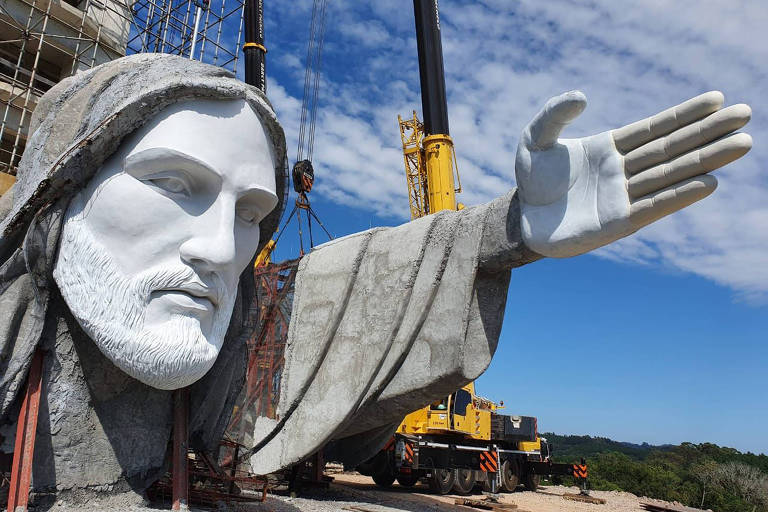 rosto de cristo gigante em obra de estátua, com trator ao fundo