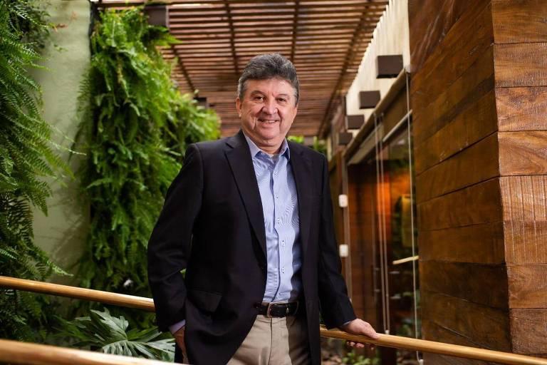 Um homem com cabelo grisalho está em um restaurante, e apoia a mão em um corrimão; ele veste blazer preto, com camisa azul e calça caqui