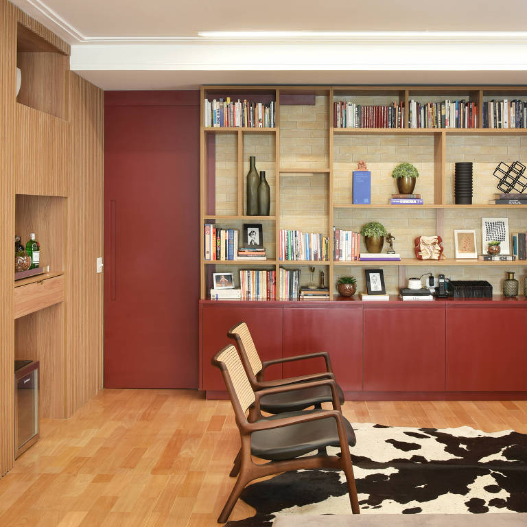 Sala com piso de madeira e parede de tijolinhos, com estante