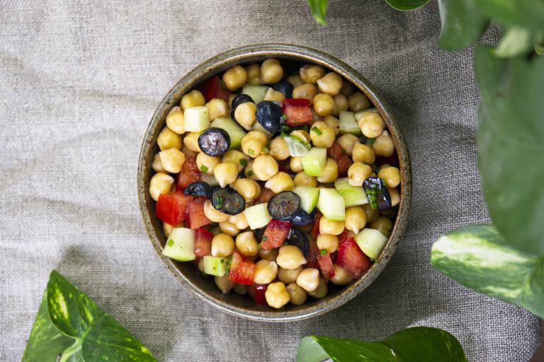 Salada de grão de bico com tomate, pepino, uvas pretas, rabanete e cebolinha