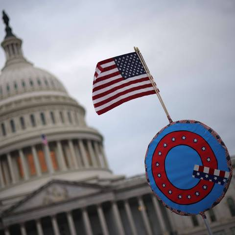 WASHINGTON, DC - JANUARY 06: Supporters of U.S. President Donald Trump fly a U.S. flag with a symbol from the group QAnon as they gather outside the U.S. Capitol January 06, 2021 in Washington, DC. Congress will hold a joint session today to ratify President-elect Joe Biden's 306-232 Electoral College win over President Donald Trump. A group of Republican senators have said they will reject the Electoral College votes of several states unless Congress appointed a commission to audit the election results.   Win McNamee/Getty Images/AFP == FOR NEWSPAPERS, INTERNET, TELCOS & TELEVISION USE ONLY ==