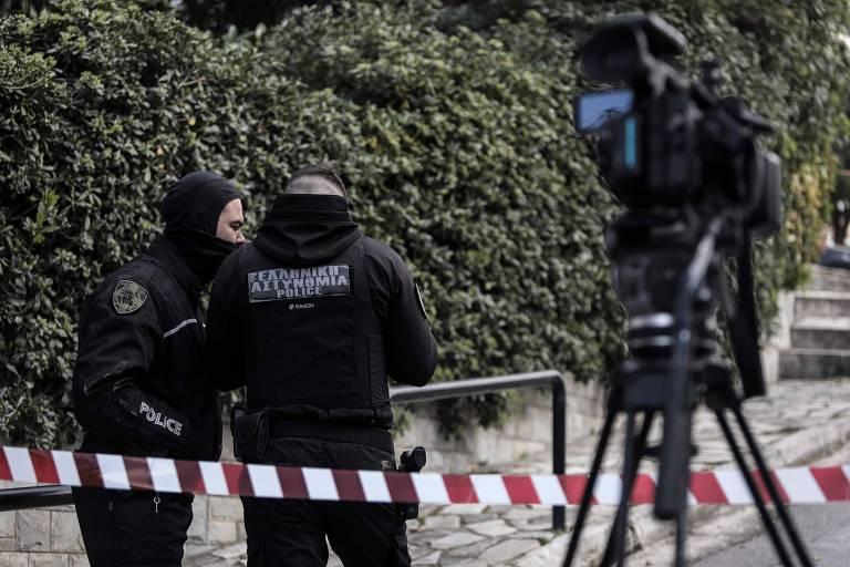 Faixa de isolamento vermelha e branco é atravessada para proteger trecho de rua, dois policiais vestidos de preto conversam ao lado de uma câmera de TV