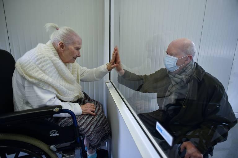 Idosa de cabelo branco preso em coque e blusa e casaco brancos, sentada, toca com a mão esquerda uma janela de vidro no lugar em que está a mão direita de um homem de máscara e casaco preto, sentado do outro lado