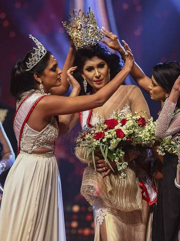 In this photograph taken on April 4, 2021, winner of Mrs. Sri Lanka 2020 Caroline Jurie (2-L) removes the crown of 2021 winner Pushpika de Silva (C) as she is disqualified by the jurie over the accusation of being divorced, at a beauty pageant for married women in Colombo. (Photo by - / AFP) ORG XMIT: IK10635