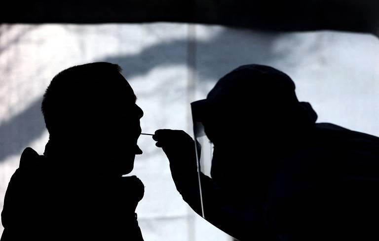 Silhuetas de um homem com a boca aberta e outro colocando um cotonete para colher amostra para teste