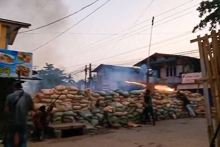 Manifestantes lançam fogos de artifício por trás de barricada na cidade de Bago, em Mianmar