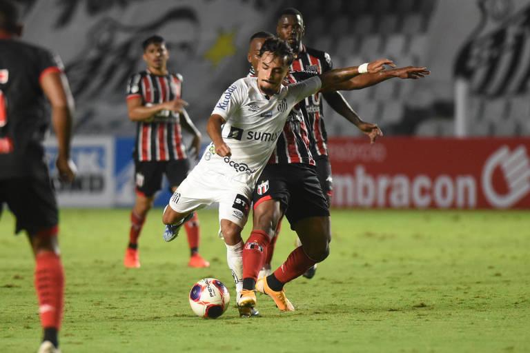 Jogador do Santos finaliza bola durante partida contra o Botafogo de Ribeirão Preto