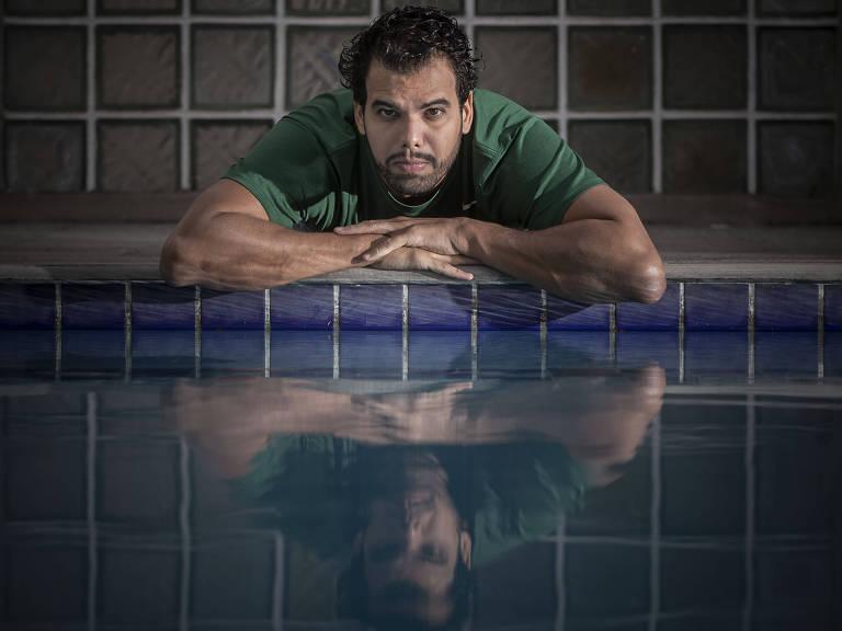 Andre Brasil, com cabelo e barba crescidos, se debruça à beira de uma piscina com olhar triste