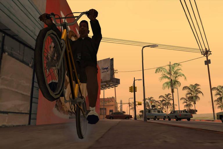 jovem negro empina a bicicleta enquanto anda por ruas de cidade no pôr-do-sol