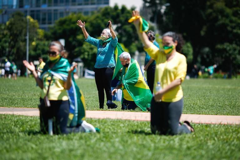 Em primeiro plano, duas mulheres estão ajoelhada no gramado; uma tem a bandeira do Brasil como capa. Atrás, um homem também está ajoelhado e, ao seu lado, há uma mulher com os braços erguidos