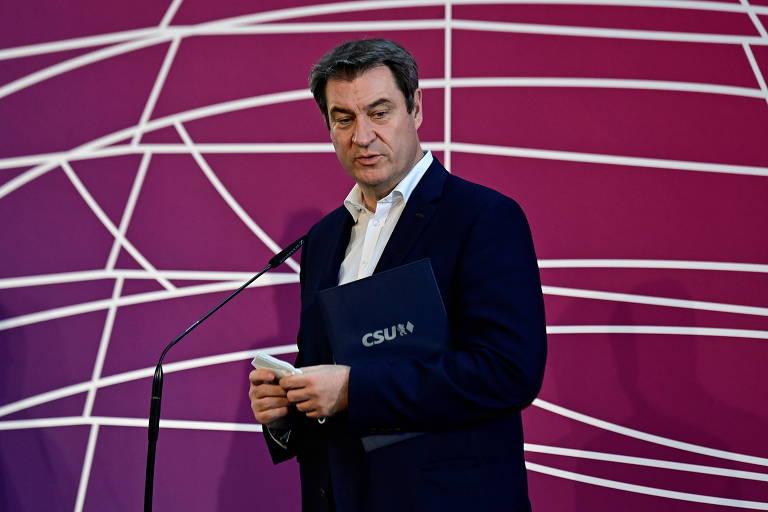 Homem de terno preto e camisa branca em frente a microfone, com fundo bordô de linhas brancas