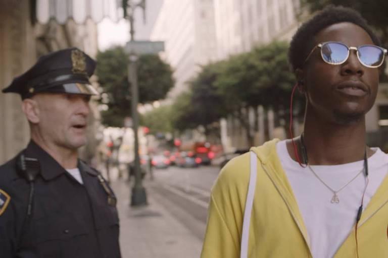 Jovem negro em frente a policial branco