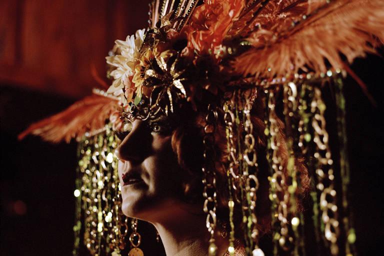 performer burlesco andrógeno usa uma grande coroa, repleta de detalhes brilhosos