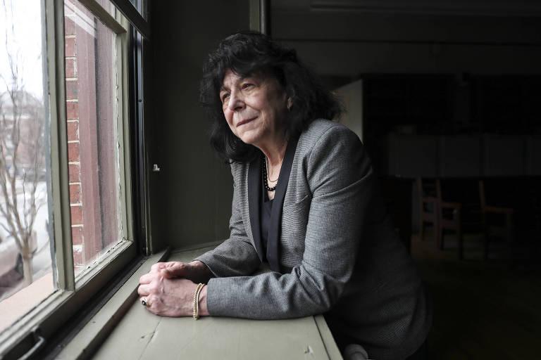 Donna Holaday, prefeita de Newburyport, é uma mulher branca e de cabelo preto; usando uma blusa cinza, ela está apoiada em uma mesa enquanto observa uma janela