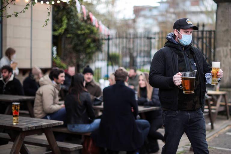 Homem carrega copos com cerveja em pub em Londres