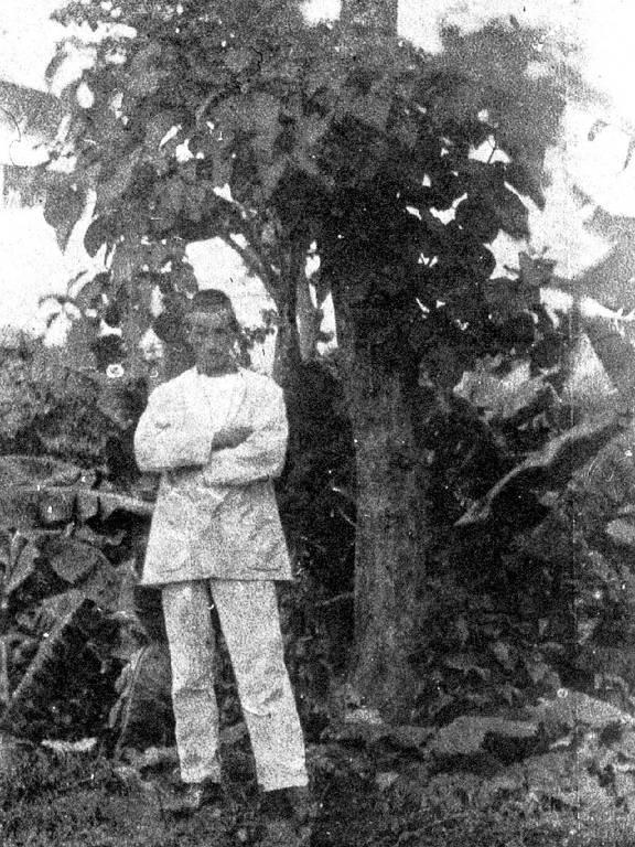 rimbaud cruza os braços perto de árvore