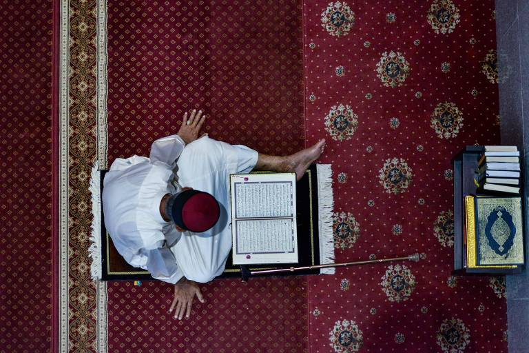 Visto de cima, homem vestido de branco, sentado em tapete vermelho, lê livro