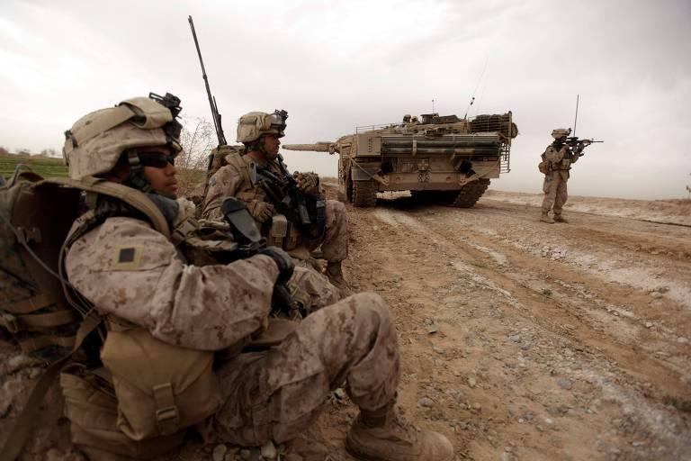 Soldados americanos patrulham estrada afegã protegidos por um tanque dinamarquês, em 2010