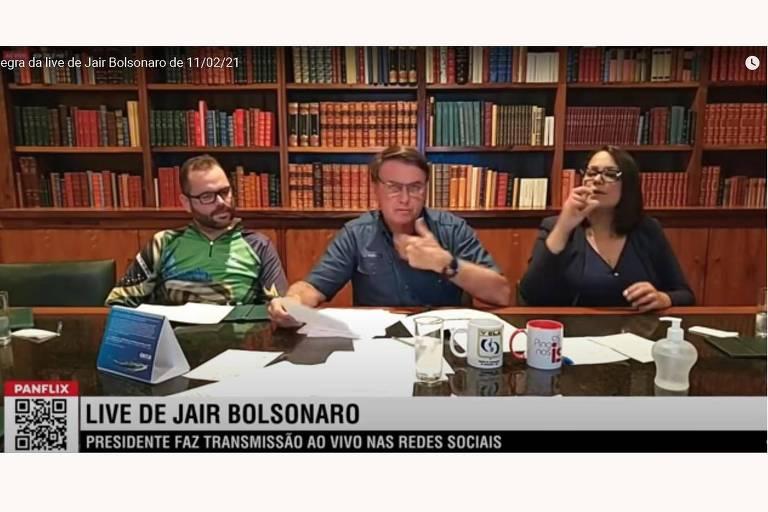 Bolsonaro ao centro da mesa, com uma mulher do lado direito dele na foto e um homem do lado esquerdo. A mesa está repleta de papéis e, ao fundo, há uma estante de livros