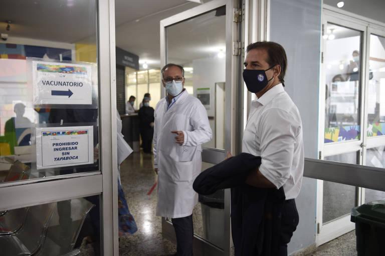Luis Lacalle Pou de máscara, segurando o paletó na mão, na porta de centro de vacinação