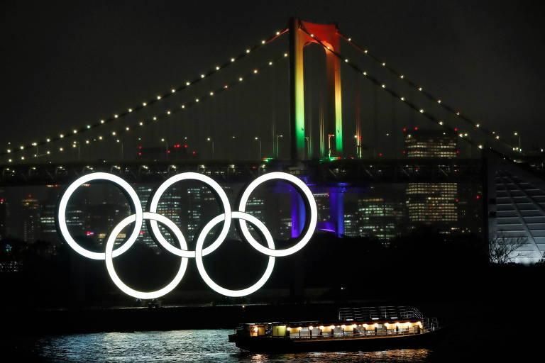 Ponte de Tóquio é iluminada com as cores dos anéis olímpicos, atrás de uma escultura dos anéis iluminados em baía de Tóquio