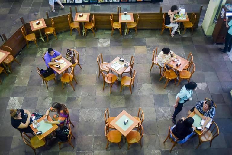 foto do alto mostra mesas e cadeiras do mercado público de Porto Alegre, algumas delas com pessoas ocupando