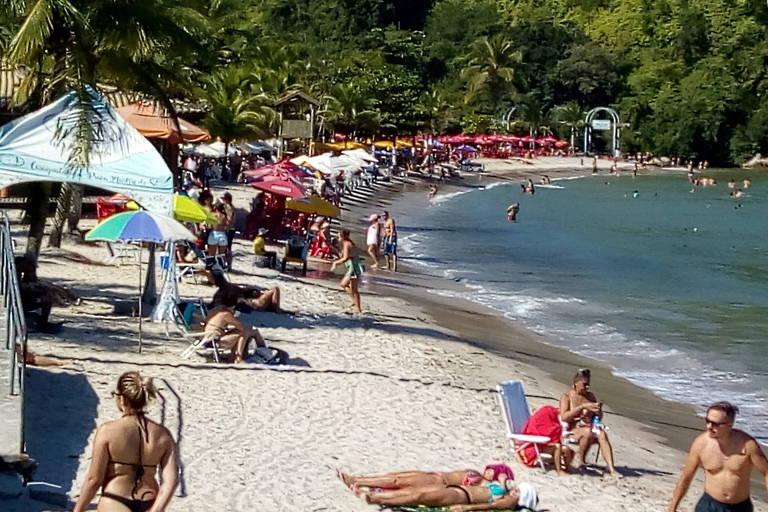 Faixa de areia com banhistas de biquini, embaixo de guarda-sois.