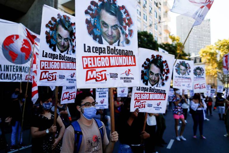 """Manifestantes seguram placas com os dizeres """"cepa Bolsonaro, perigo mundial"""" durante protesto próximo à embaixada brasileira em Buenos Aires"""