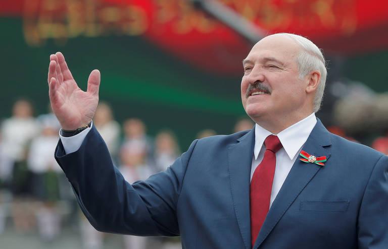 Homem careca de bigode, gravata vermelha, camisa branca e terna azul cinzento gesticula com o braço direito