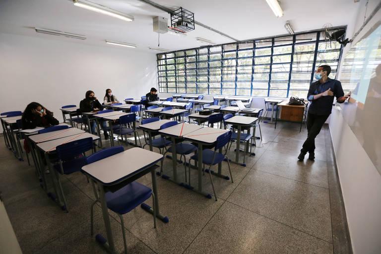 Quatro alunos assistem aula de um professor. Todos usam máscaras e a sala conta com muitas carteiras vazias em volta dos alunos.
