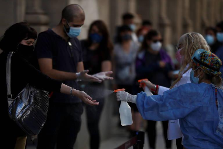 Funcionários higienizam a mão de pessoas que aguardam para fazer o teste de coronavírus em Buenos Aires