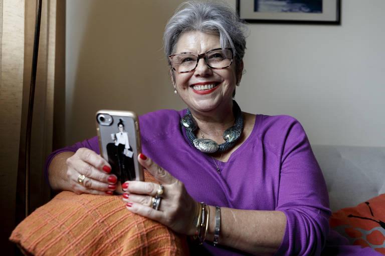 Rosangela posa sentada em um sofá, com o celular em mãos, sorrindo para a câmera. Ela é branca, tem cabelos grisalhos, veste um colar, pulseiras, anéis, óculos e uma blusa roxa. Usa batom vermelho, da mesma cor que suas unhas.