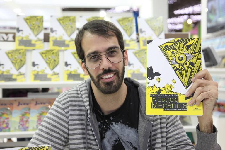 homem branco de barba e óculos mostra livro colorido