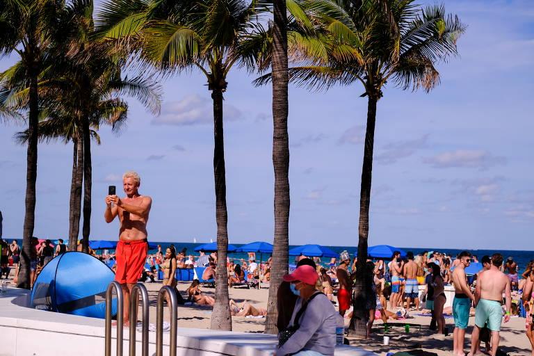 Homem faz selfie enquanto pessoas se aglomeram em praia de Fort Lauderdale, na Flórida (EUA), em meio à pandemia