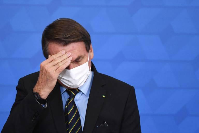 Sentado, usando máscara, Jair Bolsonaro coça a testa
