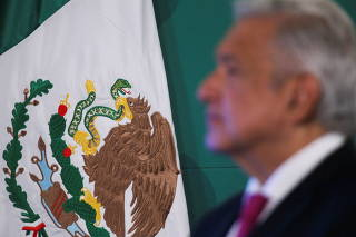 The Mexican flag is pictured next to Mexico's President Andres Manuel Lopez Obrador during a news conference at the National Palace in Mexico City