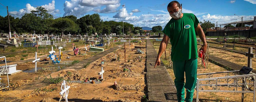 Homem indígena trajando verde e usando máscara passa por caminho estreito ao redor do qual há cruzes brancas fincadas na terra revirada; ele aponta uma delas