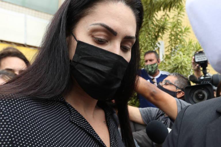 Mulher de máscara sendo conduzida por policiais com multidão envolta, filmando