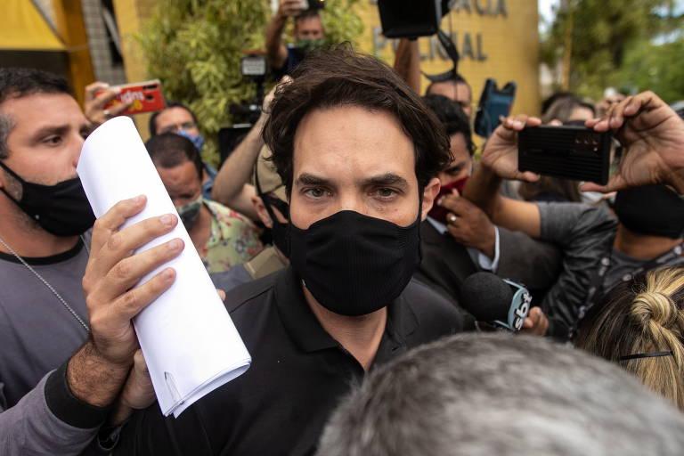Homem de máscara sendo conduzido por policiais com multidão envolta, filmando