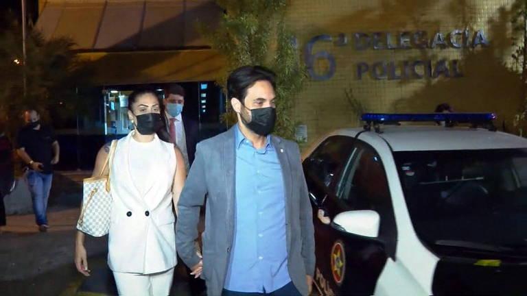 Mulher de roupa branca e homem de roupa azul de mãos dadas saindo da delegacia, com carro de polícia ao lado
