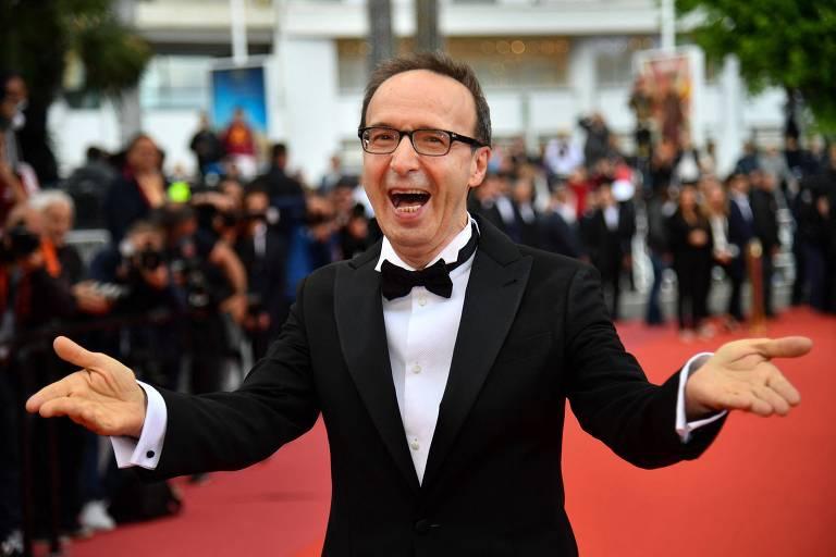Homem branco usa roupa preta formal em tapete vermelho. Ele sorri e abre suas mãos
