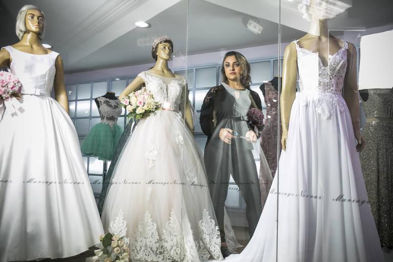 Bia em meio a manequins com vestidos de noiva