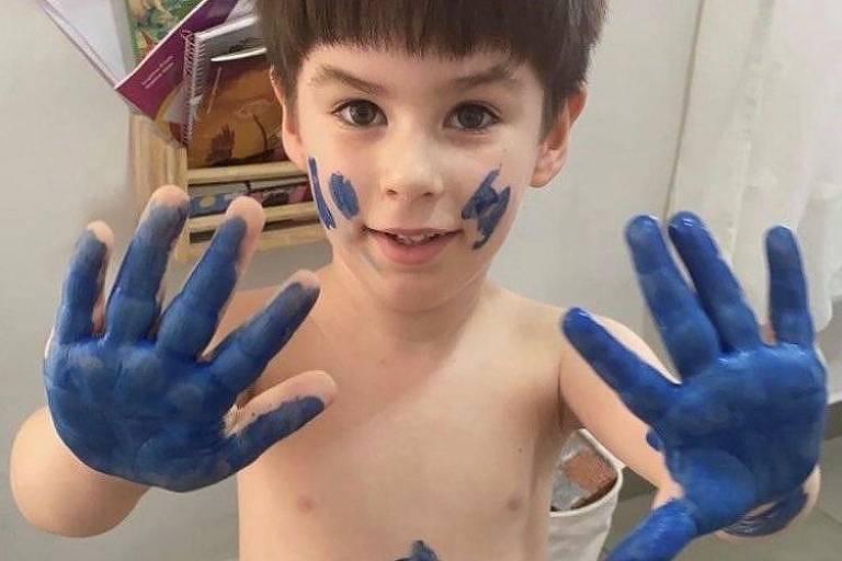 Menino branco, moreno e sem camisa mostra as mãos sujas de tinta azul
